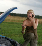 Young woman with broken car. Young blond woman with her broken car. The girl is angry Royalty Free Stock Images