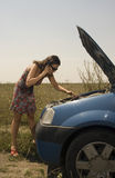 Young woman and broken car. Young woman examining the engine of a broken car and asking for help on the mobile phone Stock Photo
