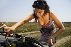 Young woman and a broken car. Young woman bent over the engine of a broken car making a funny face Stock Image