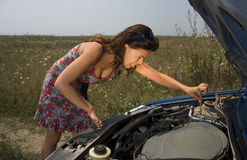 Young woman and a broken car. Young woman bent over the engine of a broken car making a funny face Royalty Free Stock Photos