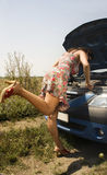 Young woman and broken car. Young woman bent over the engine of a broken car - side view Royalty Free Stock Image