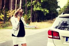 Young woman with broken car calling for help stock photo