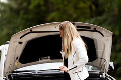 Young woman with broken car calling for help Stock Photography
