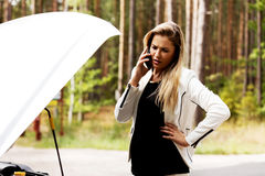 Young woman with broken car calling for help Royalty Free Stock Photography