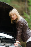 Young woman at broken car. In the forest Stock Image