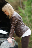 Young woman at broken car. In the forest Royalty Free Stock Photography