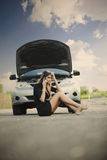 Young woman with broken car Stock Images