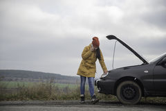 Young woman with broken car. In the middle of the road Stock Photo