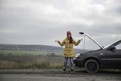 Young woman with broken car. In the middle of the road Royalty Free Stock Images