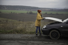 Young woman with broken car. In the middle of the road Stock Images
