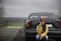 Young woman with broken car. In the middle of the road Stock Image