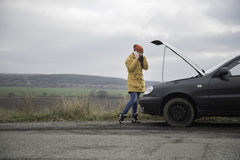 Young woman with broken car. In the middle of the road Royalty Free Stock Photography