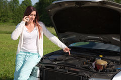 Young woman at a broken down car Royalty Free Stock Image