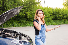 Young woman with broken down car and hood open call for help Royalty Free Stock Photo