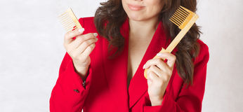 A young woman and a broken hair comb. A young woman and a broken wooden made hair brush Stock Photos