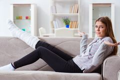 The young woman with broken leg at home. Young woman with broken leg at home royalty free stock photo