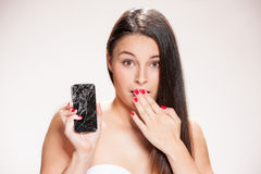 Young woman with broken smartphone. Scared young woman with broken smartphone stock photo