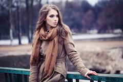 Young woman in brown coat. Outdoors Stock Image