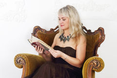 Young woman in brown dress sits Royalty Free Stock Photo