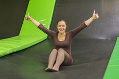 young woman in brown fit dress on trampoline in trampoline center. vertical photo. Happy girl on trampoline. Happy young woman on royalty free stock photography