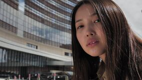 Asian girl poses in the city center against the backdrop of buildings