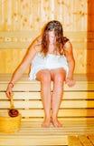 Young woman with brown hair enjoying sauna wellness. Stock Photo