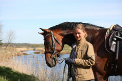 Young woman and brown horse together on the river coast Royalty Free Stock Photos