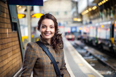 Young woman in brown winter coat waiting on train station Stock Photography