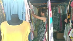 Woman choosing clothes at the market stock video footage