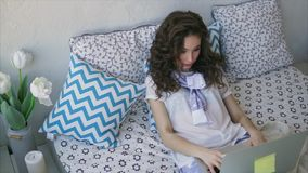 Young woman browsing incoming messages on laptop mail in the bedroom. A young pretty woman looks through the incoming messages to the laptop`s mail in the stock footage