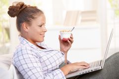 Young woman browsing Internet in bed smiling. Young woman browsing Internet in bed, using laptop, smiling, eating yoghurt Royalty Free Stock Photo