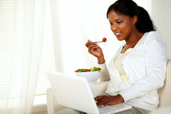 Young woman browsing the internet eating a salad Royalty Free Stock Images