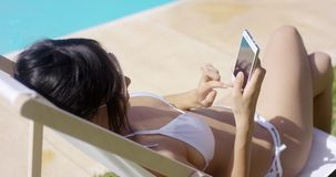 Young woman browsing on a mobile in the summer sun stock video footage