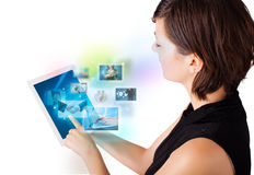 Young woman browsing pictures on modern tablet Stock Images