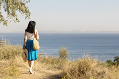 Young woman (brunette) in a blue skirt and hat looks at sea. Selective focus Royalty Free Stock Photo