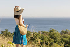 Young woman (brunette) in a blue skirt and hat looks at sea. Selective focus Stock Image