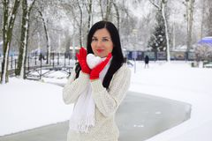 The young woman the brunette holds a snowball in the form of heart. The woman is dressed in a white knitted woolen sweater and red gloves. It is in the winter stock photos