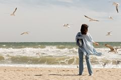 Young woman brunette in a light blue cardigan and jeans, with. A backpack, walks along the beach and feeds gulls. Selective focus Stock Images