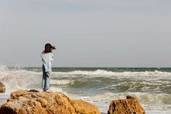 Young woman brunette in a light blue cardigan and jeans, with. A backpack, walks along the beach. Selective focus Royalty Free Stock Image
