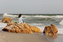 Young woman brunette in a light blue cardigan and jeans, with. A backpack, walks along the beach. Selective focus Stock Images