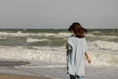 Young woman brunette in a light blue cardigan and jeans, with. A backpack, walks along the beach. Selective focus Royalty Free Stock Photos