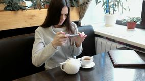 Young woman brunette pictures of teapot and Cup in a cafe on her cell phone. Front view. Young woman brunette pictures of teapot and Cup in a cafe on her cell stock video