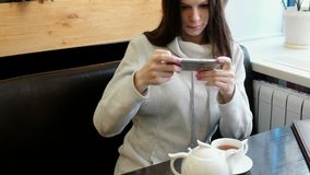 Young woman brunette pictures of teapot and Cup in a cafe on her cell phone. Front view. Young woman brunette pictures of teapot and Cup in a cafe on her cell stock footage