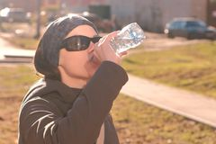 Young woman brunette in sun glasses drinks water from the bottle on the street. royalty free stock photography
