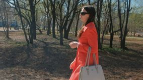 Young woman brunette in sunglasses in red coat walks in the spring Park. Young woman brunette in sunglasses in red coat walks in the spring Park stock footage