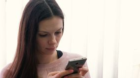 Young woman brunette is typing a message on her mobile phone and looking at screen. Young woman brunette is typing a message on her mobile phone and looking at stock video footage
