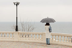 Young woman brunette in a white coat walks along the promenade Stock Photography