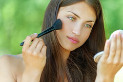 Young woman is brushed powder on Royalty Free Stock Photos