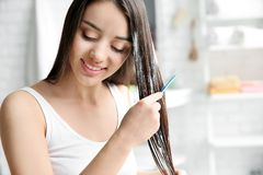 Young woman brushing hair after applying mask. In bathroom stock photo