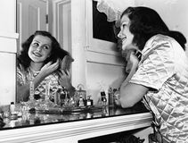 Young woman brushing hair at dressing table Royalty Free Stock Photos